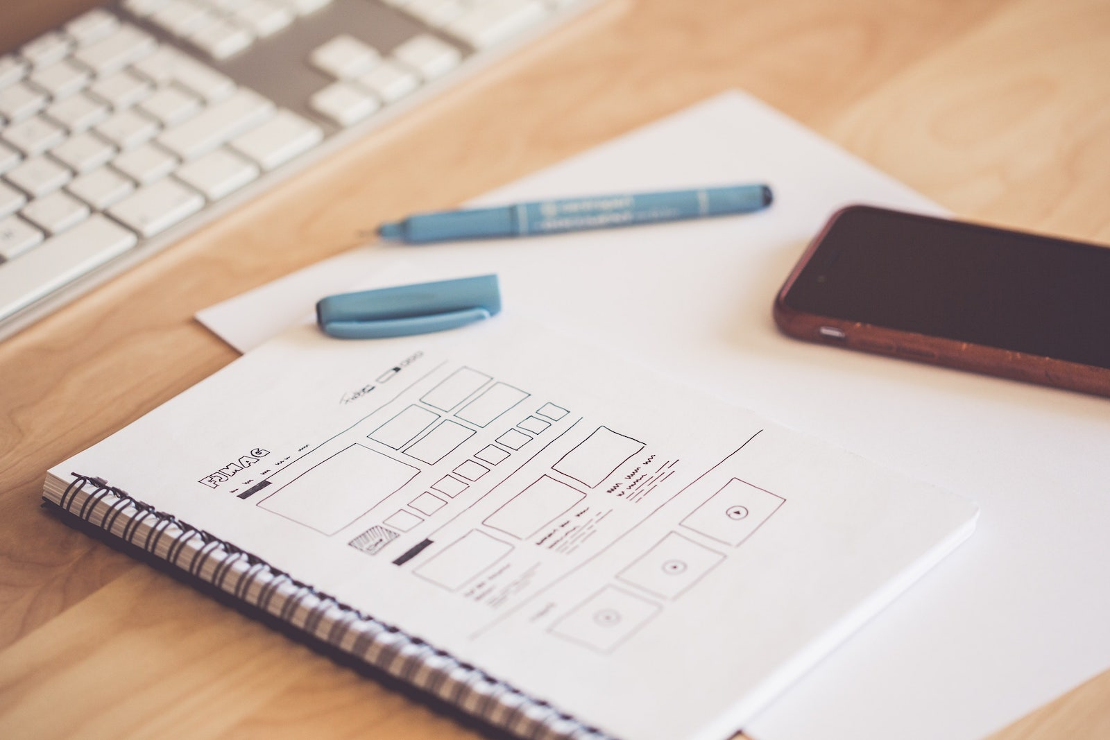 a notebook with a wireframe drawing of a website design
